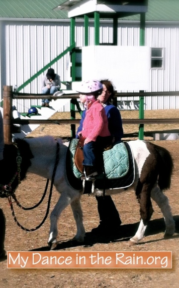She's a natural! Now only needing minimal supprt and riding without mommy.